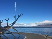 De boog van het beroemde staalbeeldhouwwerk Solfar/Zonreiziger in IJsland en een blauwe hemelmening van Reykjavik's-waterkant stock fotografie