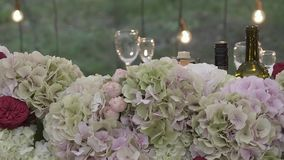 De boog voor de jonggehuwden is verfraaid met bloemen en glazen stock footage
