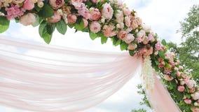 De Boogdecoratie van de huwelijksbloem Huwelijksboog met bloemen wordt verfraaid die stock footage