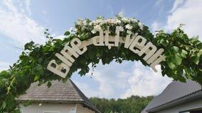 De Boogdecoratie van de huwelijksbloem Huwelijksboog met bloemen wordt verfraaid die stock video