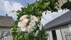 De Boogdecoratie van de huwelijksbloem Huwelijksboog met bloemen wordt verfraaid die stock videobeelden