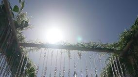De Boogdecoratie van de huwelijksbloem op zonachtergrond stock videobeelden