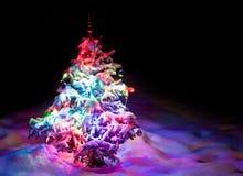 De boom van het lichtgevende Nieuwjaar onder poedersneeuw. Stock Afbeelding
