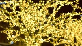 De boom was verfraait garlandswit gouden bollen Kerstmisstraatlantaarns Close-upmening, onduidelijk beeld stock videobeelden