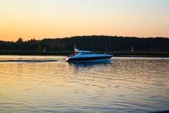 De boot drijft op een brede rivier bij zonsondergang stock foto
