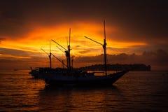 De boot en de zonsondergang van silhouetpenisi in Sorong, West-Papoea Stock Afbeelding