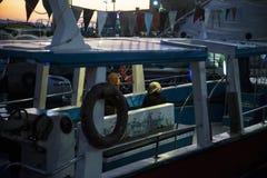 De boot komt aan de visserijhaven binnen bij zonsondergang stock afbeeldingen