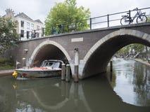 De boot komt van onder brug over oude gracht in Nederlandse stad te voorschijn van stock afbeelding