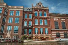 De boot legde aan kant van tree-lined kanaal, baksteengebouwen en zonnige blauwe hemel in Amsterdam vast Royalty-vrije Stock Fotografie