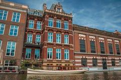 De boot legde aan kant van tree-lined kanaal, baksteengebouwen en zonnige blauwe hemel in Amsterdam vast Stock Foto's
