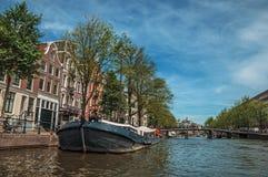 De boot legde aan kant van tree-lined kanaal, brug, oude gebouwen en zonnige blauwe hemel in Amsterdam vast Royalty-vrije Stock Afbeeldingen