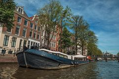 De boot legde aan kant van tree-lined kanaal, brug, oude gebouwen en zonnige blauwe hemel in Amsterdam vast Royalty-vrije Stock Foto
