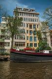 De boot legde aan kant van tree-lined kanaal, oude gebouwen en zonnige blauwe hemel in Amsterdam vast Royalty-vrije Stock Afbeeldingen