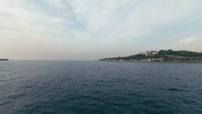 De boot maakt snel een cirkel rond het eiland met mooie groene gebieden stock footage