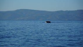 De boot met vluchtelingen zwemt aan kust stock afbeelding