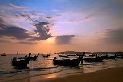 De boot op het verblijf van de zonsondergangtijd alleen op het strand. Stock Foto
