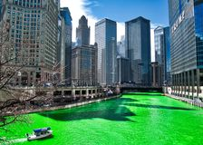 De boot reist over de Rivier van Chicago die groen voor St Patrick ` s dag geverft is aangezien de menigten scène omringen stock afbeeldingen