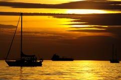 De boot van het zeil bij de zonsondergang Stock Afbeelding