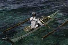 De boot van mensenrijen in fonkelende open oceaan stock foto's