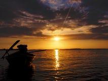 De boot van de silhouet lang-staart in zonsondergangtijd stock afbeelding