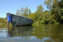 De boot wordt vastgelegd door een ketting aan een kolom stock afbeelding