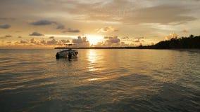 De bootrotsen op de golven in de stralen van de zonsondergang stock footage