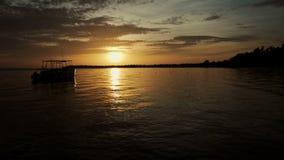 De bootrotsen op de golven in de stralen van de zonsondergang stock video