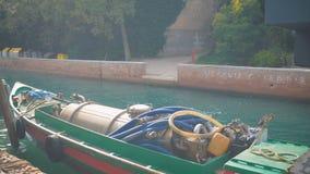 De boottribunes van de loodgieterswerkdienst in een smal kanaal in Venetië worden geparkeerd dat stock videobeelden