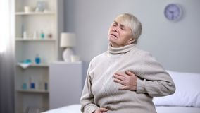De borst die van de bejaardeholding, plotseling hartaanval voelen, gezondheidsproblemen stock foto