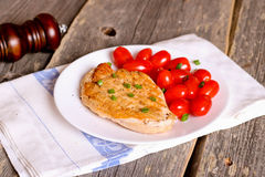 De borst van de lapje vleeskip met kersentomaten op een witte plaat Stock Fotografie