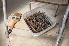 De borstel en de spijkers in de doos zijn op de trede van ladder stock foto