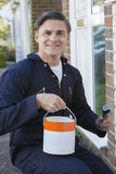 De Borstel en Tin Painting Outside Of House van de mensenholding stock foto's