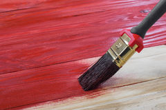 De borstel schildert een Houten Raad aan Rood Royalty-vrije Stock Foto's
