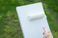 De borstel van de verfrol is geschilderd wit op de cementvloer Stock Fotografie