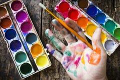 De borstel van de waterverfverf om de hand van de kunstenaar in multi-colored verf op houten holding als achtergrond te schildere Royalty-vrije Stock Fotografie