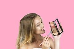De borstel van de meisjesholding en eyeshagow palet geïsoleerde roze achtergrond stock foto's