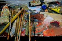 De borstels en het palet van de kunstenaarsverf op achtergrond stock afbeelding