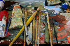 De borstels en het palet van de kunstenaarsverf op achtergrond stock foto's