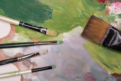 De borstels en de olieverf van de kunstenaarsverf op houten artistiek palet B Royalty-vrije Stock Afbeeldingen