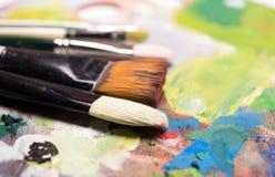 De borstels en de olieverf van de kunstenaarsverf op houten artistiek palet B Stock Foto's