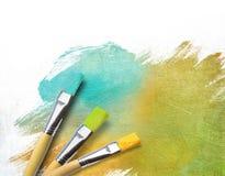 De borstels van de kunstenaar met een half gebeëindigd canvas Stock Afbeeldingen