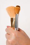 De borstels van de make-up die door hand worden gehouden royalty-vrije stock afbeelding