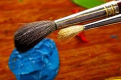 De borstels van de olieschilder ` s en blauwe kleur Stock Foto