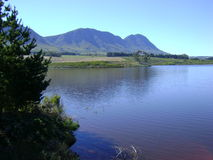 De Bos dam Hermanus. View over De Bos dam in Hermanus Western Cape. Mountains in the back ground with tree in the fore front Stock Photo