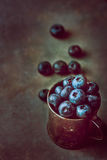De bos van blueberried in roestige metaalkruik op donkere steen concrete achtergrond Verspreide bessen Creatief gestemd beeld met Stock Fotografie