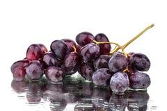 De bos van rode druiven op een witte spiegelachtergrond met bezinning en waterdalingen isoleerde dicht omhoog stock afbeeldingen