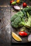 De bos van verse groene broccoli met groenteningrediënten op donkere rustieke houten achtergrond, sluit omhoog Stock Afbeeldingen