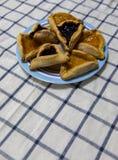De Bosbes en de abrikoos van Hamantashpurim blokkeren koekjes op gekleurde plaat op tafelkleed met blauwe vierkantenachtergrond royalty-vrije stock afbeelding