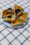 De Bosbes en de abrikoos van Hamantashpurim blokkeren koekjes op gekleurde plaat op tafelkleed met blauwe vierkantenachtergrond stock afbeelding