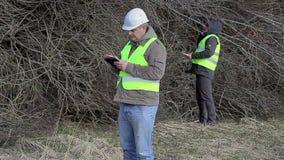 De bosingenieurs met tabletpc en cel telefoneren stock video